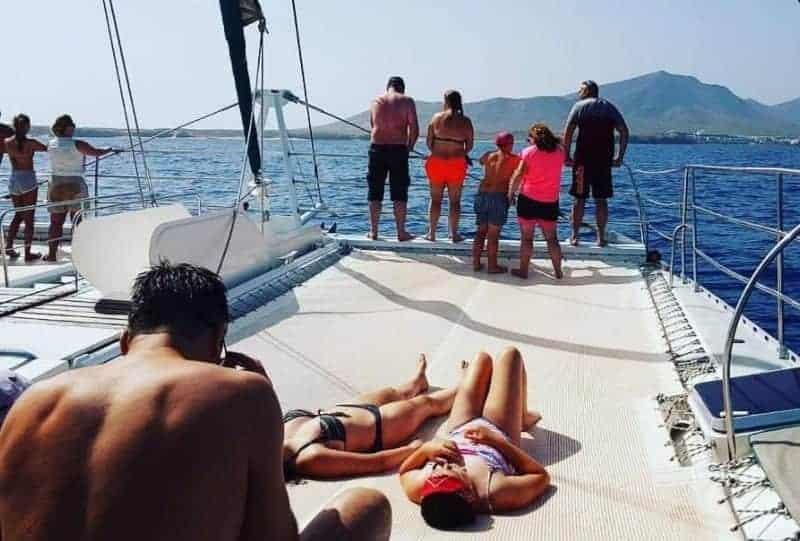 Turistas tomando el sol y disfrutando de la excursión en barco